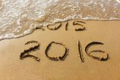 2015 and 2016 year written on sandy beach sea. Wave washes away 2015. The concept of 2015 is gone, come the new year 2016.